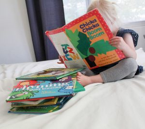 little girl reading a book next to stack of books