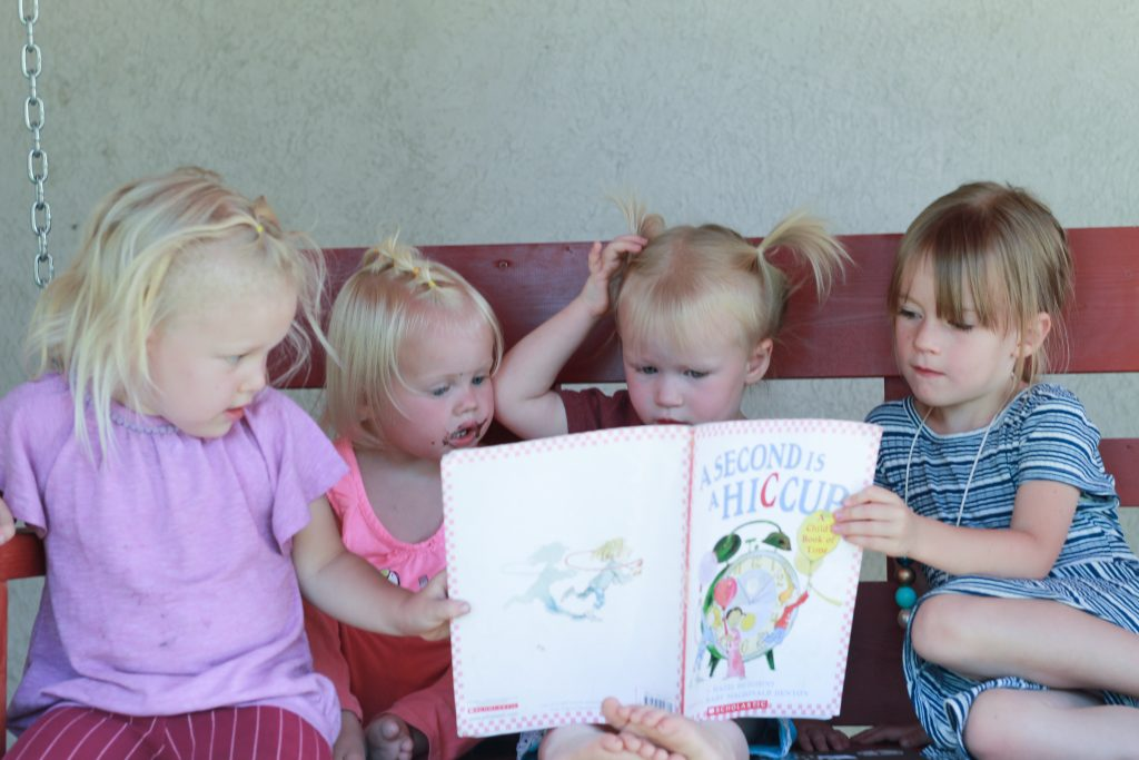 four girls reading book together on swing