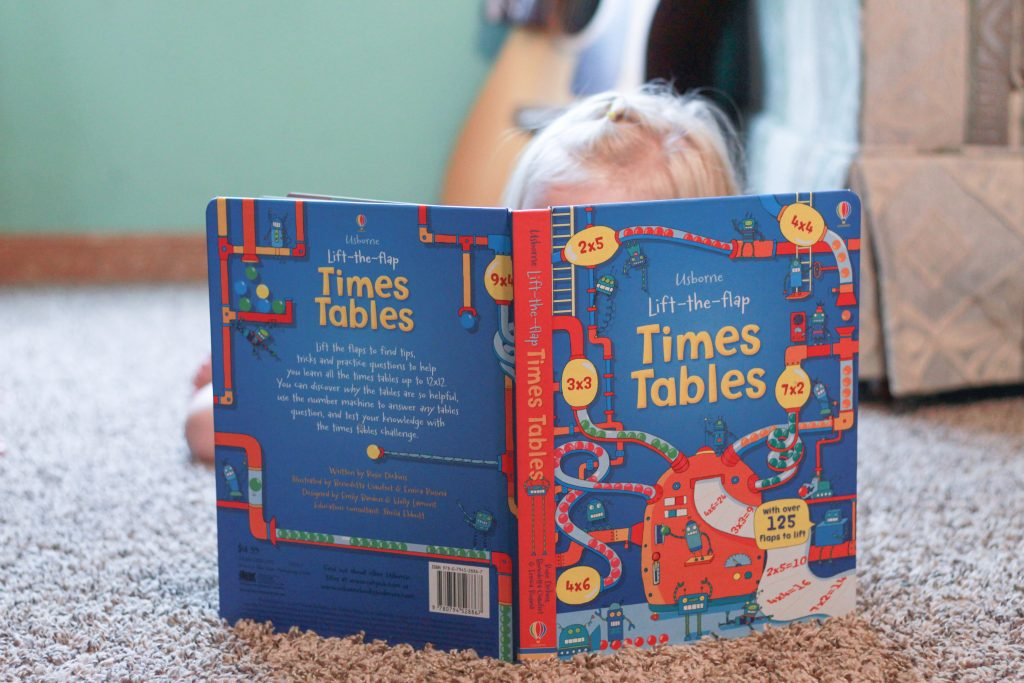 child reading Times Tables book while lying down