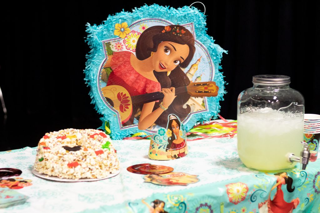 table decorated with elenor of avalor  decorations and pinata with a mason jar drink dispenser with lemonade and a popcorn cake