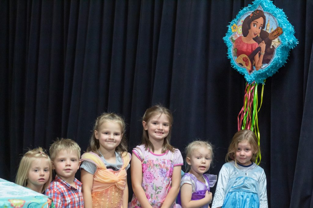 group of six children lined up next to elenor of avalor pinata