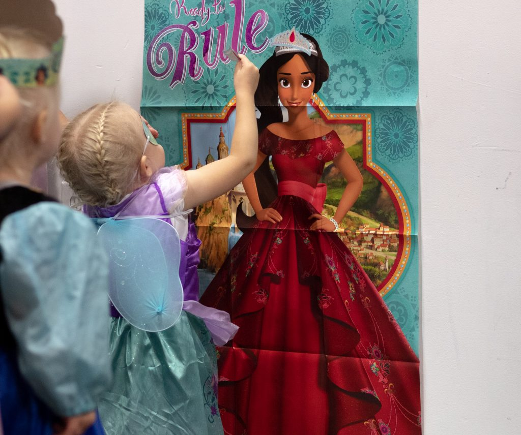 3 year old blonde girl putting a crown sticker on a princess poster
